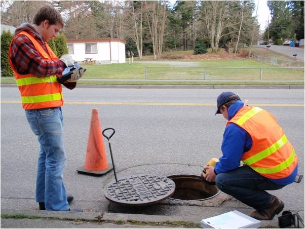 City staff looking in to open manhole inspecting stormwater drainage.