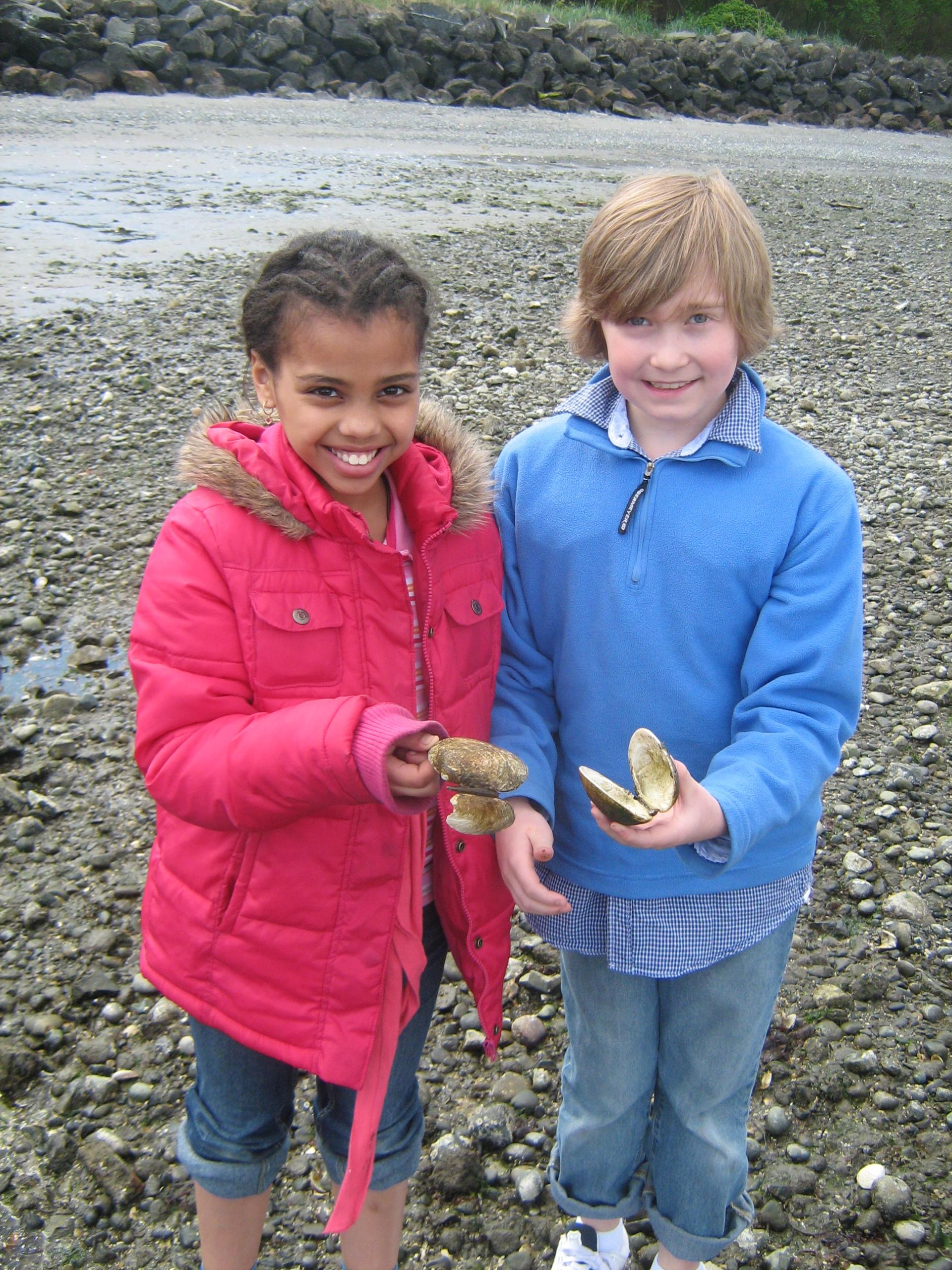 Two kids at a rocky beach, smiling and holding clam shells