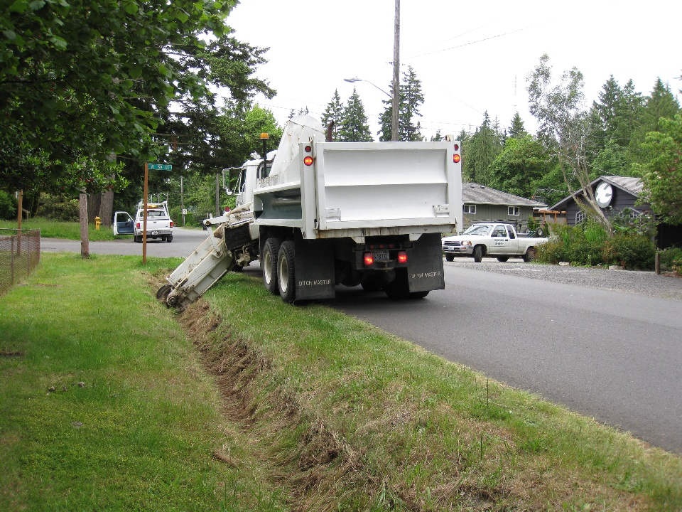 Dump truck with ditch digger equipment clearing out a grassy ditch.