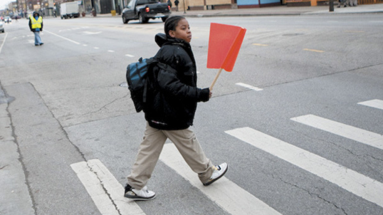 A young boy holding an orange pedestrian flag as he walks through a crosswalk.