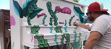 Artist Joseph Brooks painting a piano
